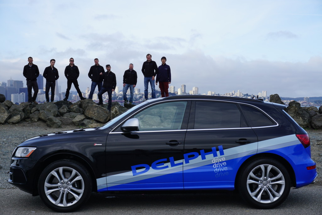 delphi engineers-standing-on-rocks-behind-delphi-autonomous-vehicle